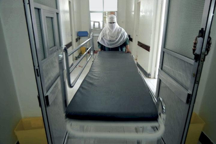 Sana'a, Yemen, 2004 - A nurse rushes a gurney down a corridor.